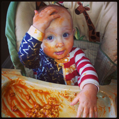 baby makes a mess playing with spaghettio's