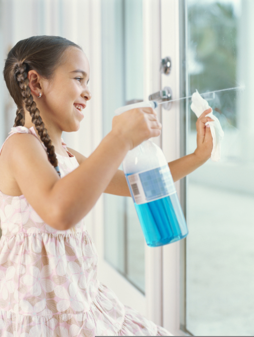 Child Spraying Cleaning Product on the Window