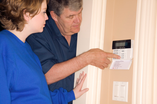 Family Setting Up Home Alarm System