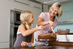 Grandmother and Granddaughter Baking Birthday Cake
