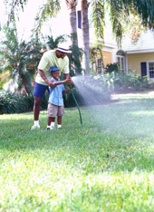 Father and Son Watering Lawn