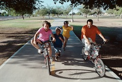 family exercising on bikes together laughing