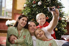 Family taking selfie in front of a Christmas tree