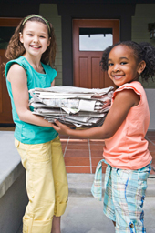 girls recycling newspaper
