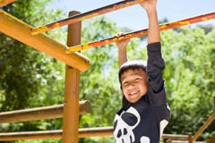 child playing on monkey bars to help his handwriting