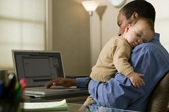 Father working from home with sleeping infant