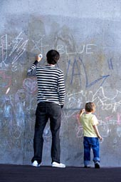 little boy drawing on a wall