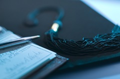 Mortarboard and checkbook with pen