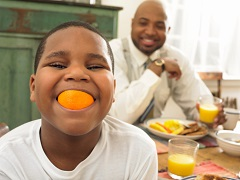 Young Boy Eating Orange
