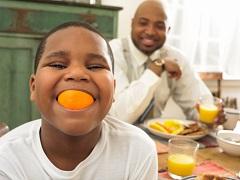Young Boy Eating Orange