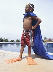 Boy by pool wearing towel as cape