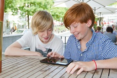 Two teenagers look at a tablet