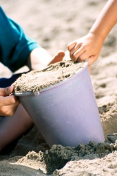 Children packing a pail with sand