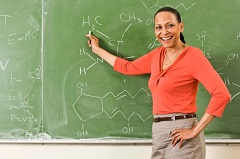 Chemistry teacher in front of chalkboard