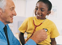 Doctor showing stethoscope to boy