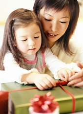 Mother and daughter wrapping a present