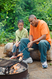Father and daughter cook while camping