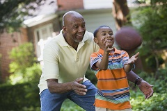 Grandfather and grandson playing football