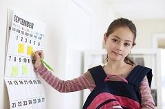Girl writing on family calendar