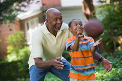 Grandfather Teaching Grandson to Catch Football