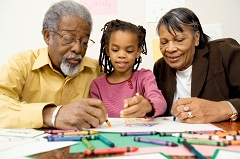Grandchild coloring a picture with her grandparents