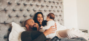 Happy parents playing with their newborn son on bed