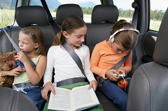 Three young girls sitting in back seat of car