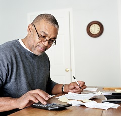 Man calculating expenses, creating budget