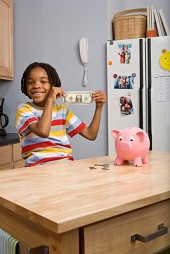 Child holding dollar by piggy bank