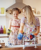 Mother & Young Daughter Smile While Cleaning