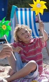Boy holding pinwheel on the beach