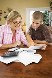 Mom paying bills with teenage son