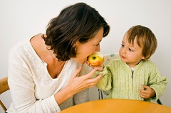 toddler sharing an apple with mom