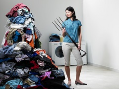 Woman with pitchfork next to large pile of laundry