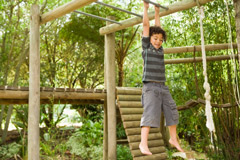 Young Boy on Jungle Gym Outside