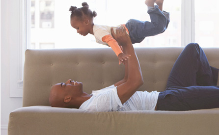 A father holds his daughter in the air while lying on a couch.