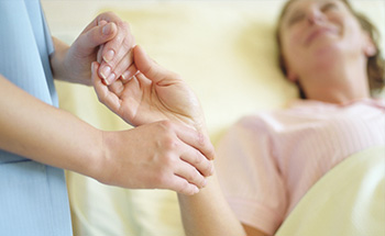 A woman's hand is held while lying on a hospital bed.